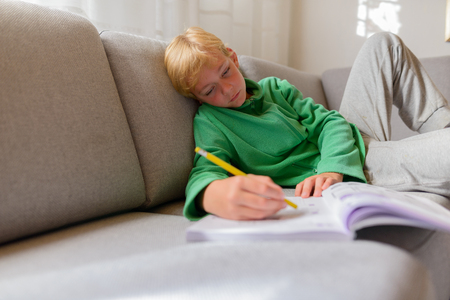 Handsome boy writing on notebook looking bored while lying on sofa at home