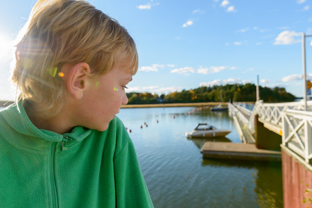 Profile view of handsome boy looking back on wooden bridge and pier along the river