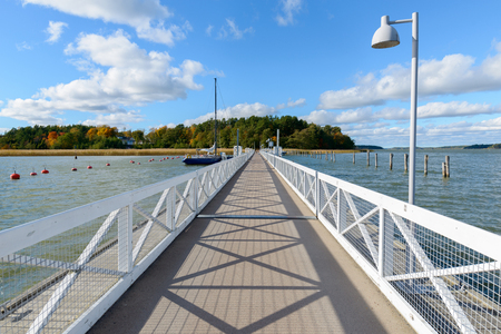 Beautiful perspective view of well-built pier leading towards the fields with clear blue sky