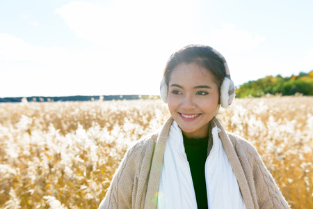 Young happy Asian woman smiling while thinking against scenic view of autumn bullrush field Stock Photo