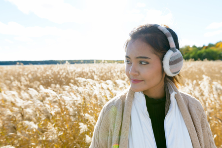 Young beautiful Asian woman thinking and looking away against scenic view of autumn bullrush field