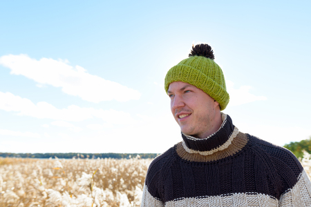 Young happy handsome man smiling while thinking against scenic view of autumn bullrush field Stock Photo