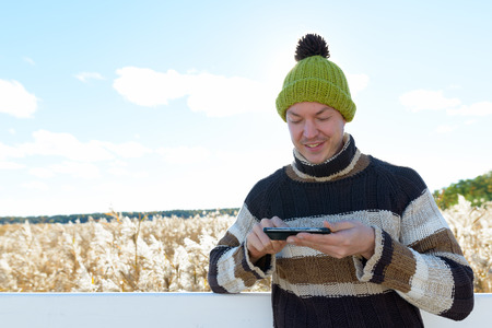 Young happy man smiling and using mobile phone against scenic view of autumn bullrush field