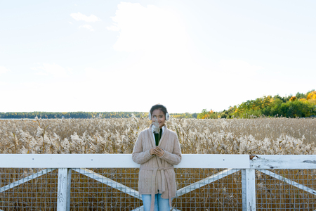 Young happy Asian woman smiling while hiding face behind grass against scenic view of autumn bullrush field Stock Photo