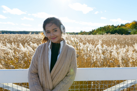 Young beautiful Asian woman against scenic view of autumn bullrush field Stock Photo