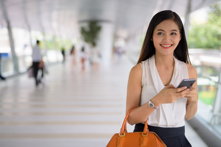 Giovane bella donna di affari asiatica che appende fuori al footbridg Archivio Fotografico - 101149093