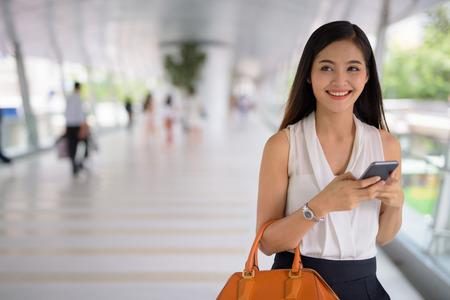 Jeune belle femme d'affaires asiatique traîner au footbridg