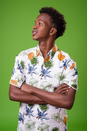 Young African tourist man ready for vacation against green backg