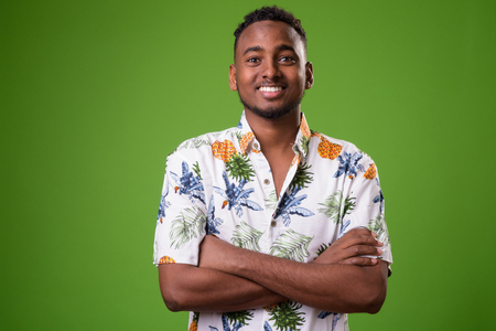 Young handsome African tourist man ready for vacation against gr