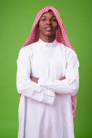 Young African man wearing traditional Muslim clothes against gre