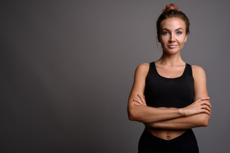Young beautiful woman ready for gym against gray background Stockfoto