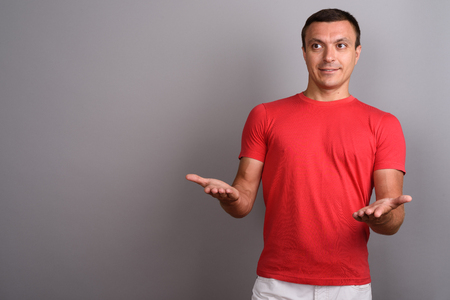Man wearing red shirt against gray background Stock Photo