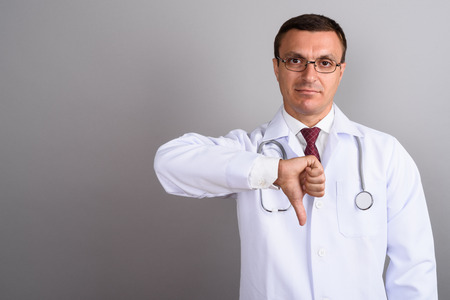Man doctor wearing eyeglasses against gray background Foto de archivo