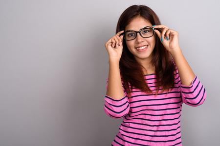 Young beautiful Indian woman wearing eyeglasses against gray bac Stock Photo