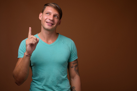 Studio shot of muscular man against brown background