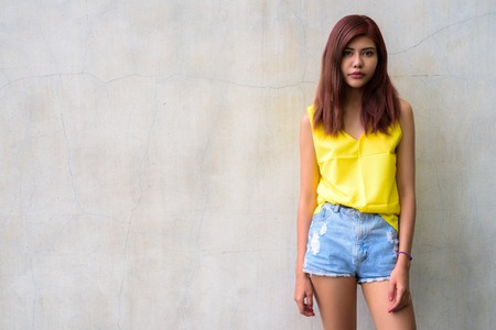 Beautiful teenager girl wearing vibrant yellow shirt