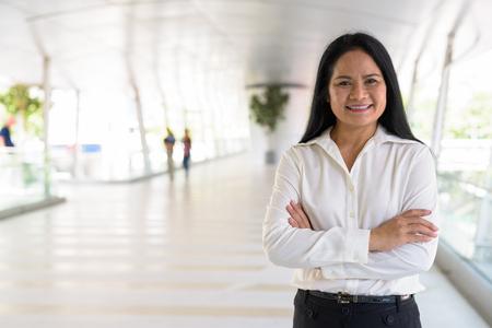 Mature beautiful Asian businesswoman relaxing at the footbridge Imagens