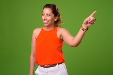 Beautiful businesswoman against green background