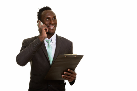 Thoughtful young happy African businessman smiling and talking o