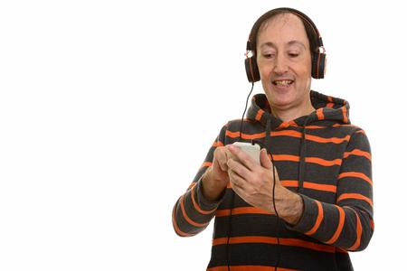 Studio shot of happy mature man smiling while using mobile phone