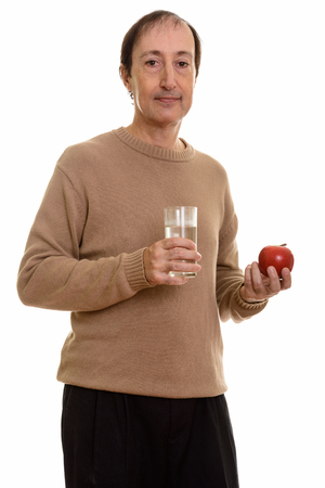 Studio shot of mature man holding glass of water and red apple