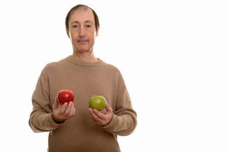 Studio shot of mature man holding red and green apple