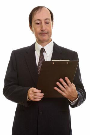 Studio shot of mature businessman reading on clipboard