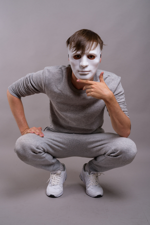 Young handsome man wearing white mask against gray background