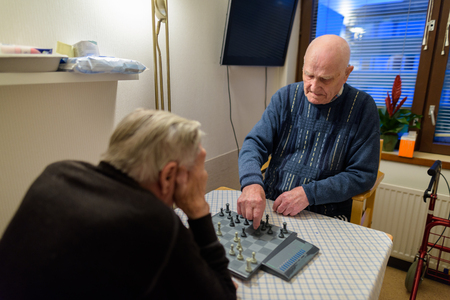Two senior men playing chess while relaxing at nursing home in T