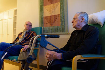 Mature man and senior man together at nursing home in Turku, Fin