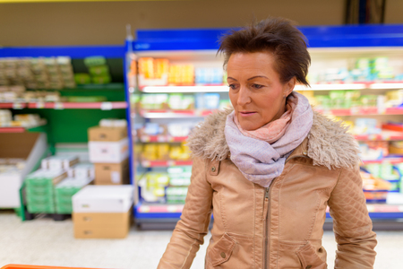 Beautiful mature woman shopping at the grocery store