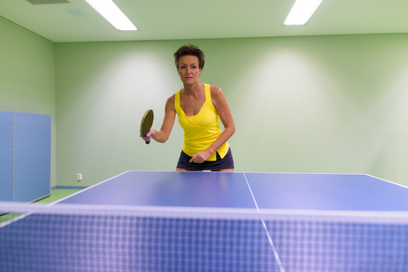 Mature beautiful woman playing table tennis indoors