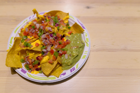 Delicious Plateful Of Nachos With Cheese And Guacamole On Wooden Stock Photo