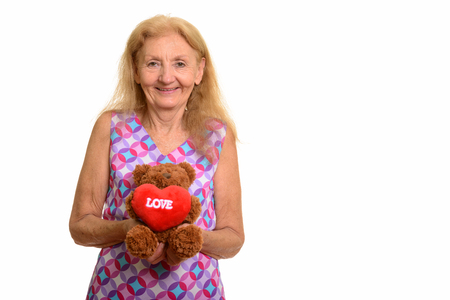 Studio shot of happy senior woman smiling while holding teddy be