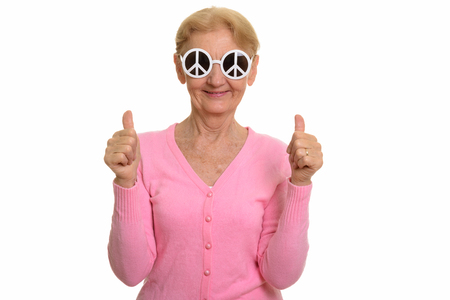 Happy senior woman smiling while wearing sunglasses with peace s