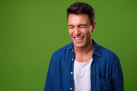 Young handsome Hispanic man against green background Banque d'images