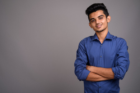 Young Indian businessman against gray background