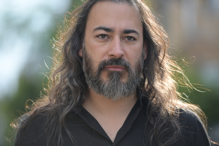 Mature handsome bearded multi-ethnic businessman with long hair in the streets outdoors Banque d'images