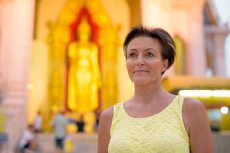 Mature beautiful Scandinavian tourist woman exploring Nakhon Pat