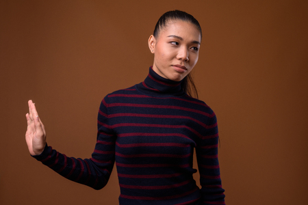 Young beautiful Asian transgender woman against brown background Stock Photo