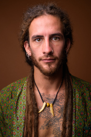 Young handsome Hispanic man with dreadlocks against brown backgr