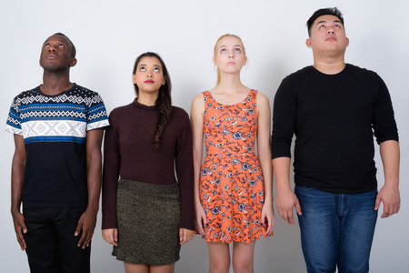 Studio shot of diverse group of multi ethnic friends looking up
