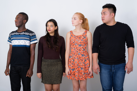 Studio shot of diverse group of multi ethnic friends looking at Stock Photo