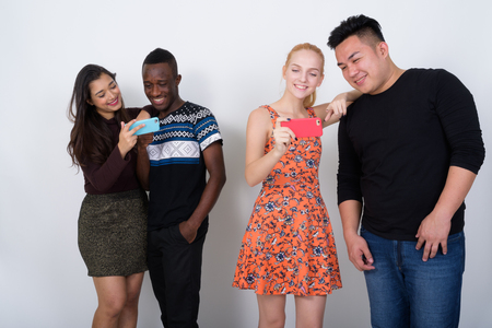 Happy diverse group of multi ethnic friends using one mobile pho Stock Photo