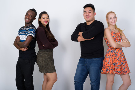 Happy diverse group of multi ethnic friends smiling with arms cr