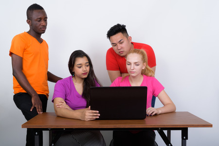 Studio shot of diverse group of multi ethnic friends using lapto Stock Photo