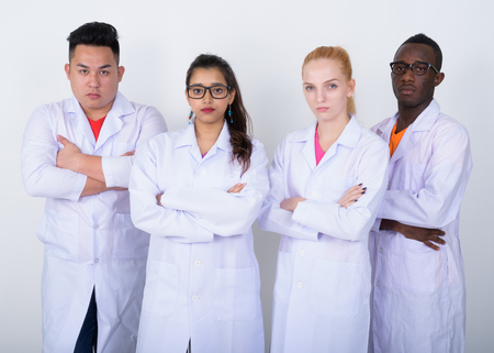 Studio shot of diverse group of multi ethnic doctors with arms c Stock Photo