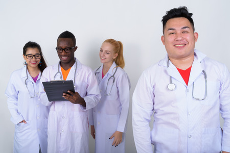 Studio shot of happy young Asian man doctor with diverse group o Stock Photo