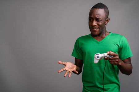Young African man wearing green shirt against gray background
