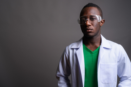 Young African man doctor wearing protective glasses against gray Stock Photo